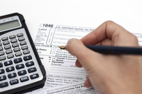 Hand filing out Tax Form